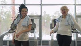 Giovane donna alta--cinque con la donna anziana che sta pedana mobile vicina video d archivio