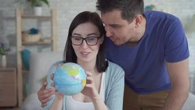 Giovane donna alta vicina e uno sguardo del giovane al globo stock footage