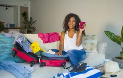 Giovane donna americana dell'africano nero felice attraente e pazzo che prepara i vestiti che imballano roba in valigia che lasci fotografie stock
