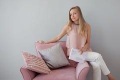 Giovane donna amichevole che si siede in una sedia con un taccuino in sue mani Un compagno piacevole immagini stock libere da diritti