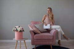 Giovane donna amichevole che si siede in una sedia con un taccuino in sue mani Interior design alla moda, un mazzo dei fiori immagine stock
