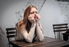 Giovane donna annoiata che si siede ad un'attesa della tavola Immagini Stock Libere da Diritti
