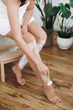 Giovane donna in asciugamano bianco che rade le gambe con il rasoio e la crema di plastica di depilazione in bagno domestico con  fotografia stock