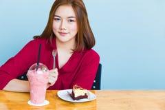 7bb4d4ccba68 Giovane donna asiatica attraente che gode del suoi dolce e smo deliziosi  fotografia stock