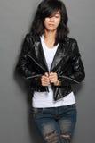 Giovane donna asiatica in bomber nero su fondo grigio fotografia stock libera da diritti
