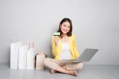 Giovane donna asiatica che compera online a casa sedendosi oltre alla fila di immagini stock libere da diritti