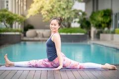 Giovane donna asiatica che fa esercizio di yoga vicino alla piscina Fotografia Stock