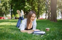Giovane donna asiatica che fa le note, mettere su un'erba verde Caffè sorridente e bevente nel parco durante il giorno Fotografia Stock Libera da Diritti