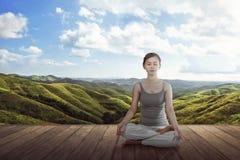 Giovane donna asiatica che fa meditazione del loto di yoga sul floo di legno Immagine Stock