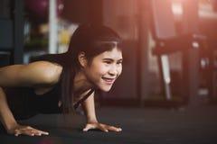 Giovane donna asiatica che fa spinta-UPS alla palestra immagini stock libere da diritti