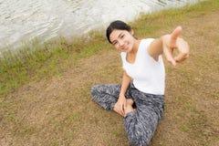 Giovane donna asiatica che gode e che si rilassa sull'erba verde fotografia stock libera da diritti