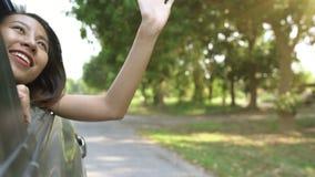 Giovane donna asiatica che gode ritenendo vento attraverso la finestra di automobile stock footage