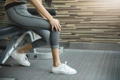 Giovane donna asiatica che ha dolore del ginocchio Immagini Stock