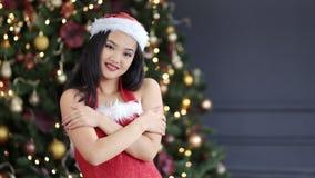 Giovane donna asiatica che indossano il vestito di Santa Claus e cappello che sorride nell'albero di Natale di stupore del fondo stock footage