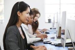 Giovane donna asiatica che lavora al computer con la cuffia avricolare in ufficio immagini stock