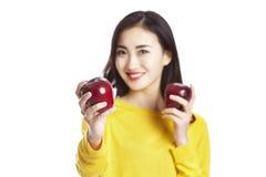 Giovane donna asiatica che mostra due mele rosse fotografia stock