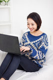 Giovane donna asiatica che per mezzo del computer portatile Immagine Stock