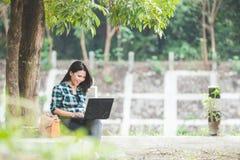 Giovane donna asiatica che per mezzo del computer portatile mentre sedendosi sul parco Fotografia Stock Libera da Diritti