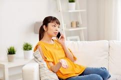 Giovane donna asiatica che rivolge allo smartphone a casa Immagini Stock