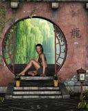 Giovane donna asiatica che si siede ad una finestra della riva del lago Immagini Stock