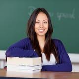 Giovane donna asiatica che si siede allo scrittorio della scuola Fotografia Stock
