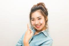 Giovane donna asiatica che sorride e che applica crema d'idratazione Fotografia Stock Libera da Diritti