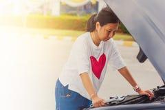 Giovane donna asiatica che tiene una chiave per la riparazione dell'automobile rotta fotografie stock