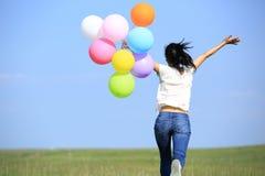 Giovane donna asiatica con i palloni colorati fotografia stock