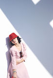 Giovane donna asiatica con il cappello rosso che si trova contro la parete fotografia stock libera da diritti