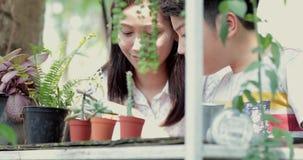 Giovane donna asiatica con il ragazzo che impara e che fa nel giardino stock footage