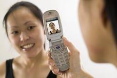Giovane donna asiatica con il telefono delle cellule Fotografie Stock