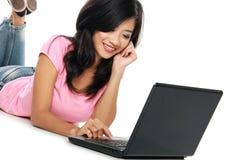 Giovane donna asiatica con un computer portatile, mettente sul pavimento isolato Immagini Stock Libere da Diritti