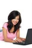 Giovane donna asiatica con un computer portatile, mettente sul pavimento isolato Fotografia Stock Libera da Diritti