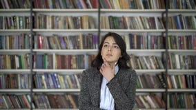 Giovane donna asiatica dei capelli neri della donna che indica ad un libro su uno scaffale per libri stock footage