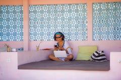 Giovane donna asiatica dei pantaloni a vita bassa attraenti e felici che lavora con il computer portatile a rilassarsi all'aperto immagine stock