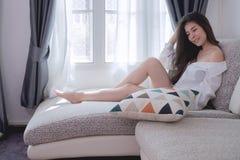 Giovane donna asiatica del fronte sorridente che si siede sul sofà in salone Fotografia Stock