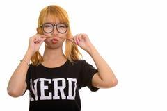 Giovane donna asiatica del nerd che gioca con i suoi capelli come baffi fotografia stock libera da diritti