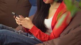 Giovane donna asiatica del ritratto che chiacchiera nella rete sociale sul cellulare stock footage