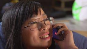 Giovane donna asiatica del ritratto che parla sullo smartphone archivi video