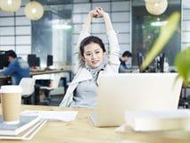 Giovane donna asiatica di affari che allunga nell'ufficio Fotografia Stock Libera da Diritti