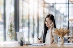 Giovane donna asiatica di affari che per mezzo del computer portatile e scrivendo sul taccuino Immagine Stock Libera da Diritti