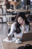 Giovane donna asiatica di affari che per mezzo dello smartphone Immagine Stock