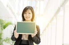 Giovane donna asiatica di affari che tiene bordo in bianco immagini stock