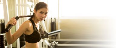 giovane donna asiatica di forma fisica in abiti sportivi che esercita i muscoli di costruzione con l'incrocio del cavo della macc immagini stock