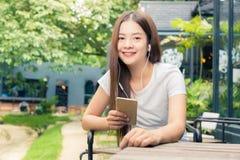 ef32f2c03dc4 Giovane donna asiatica felice attraente che si siede fuori in un liste del  giardino immagine stock
