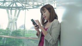 Giovane donna asiatica felice casuale attraente in aeroporto internazionale, utilizzando e controllando il suo smartphone che sta archivi video