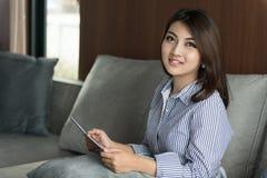 Giovane donna asiatica felice che per mezzo della compressa digitale Fotografia Stock