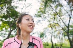 Giovane donna asiatica felice che si scalda il suo corpo allungando il suo corpo prima dell'esercizio di mattina e yoga nel parco Immagine Stock Libera da Diritti