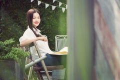 Giovane donna asiatica felice che sorride alla macchina fotografica che tiene un libro Immagine Stock