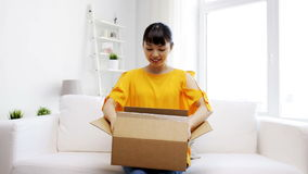 Giovane donna asiatica felice con la scatola del pacchetto a casa archivi video